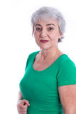Portrait of a senior woman isolated on white in a green shirt. royalty free stock photography