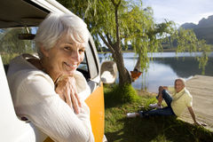 Portrait of senior woman leaning from window of camper van by lake, senior man on jetty in background Royalty Free Stock Image