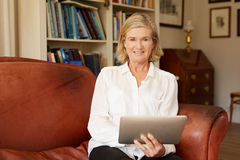 Portrait of a senior woman in living room with tablet Stock Photography