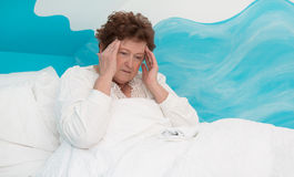 Portrait: senior woman lying ill with headache in the bed. Royalty Free Stock Image