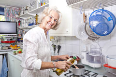 Portrait of senior woman pouring olive oil to saucepan in domestic kitchen Stock Photography