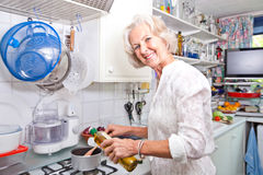 Portrait of senior woman pouring olive oil to saucepan in domestic kitchen Royalty Free Stock Images