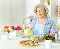 Senior woman pouring tea. Portrait of a senior woman pouring tea at kitchen Royalty Free Stock Photo