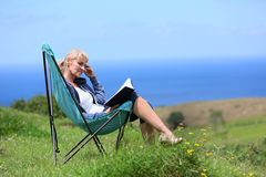Portrait of senior woman reading book in camping chair by the sea Stock Image