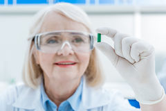 Portrait of senior woman scientist analyzing pill in hand Stock Photos