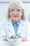 Portrait of senior woman scientist holding pills in hands Royalty Free Stock Photo