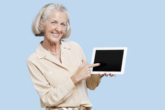 Portrait of senior woman showing tablet PC against blue background Stock Image