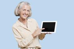 Portrait of senior woman showing tablet PC against blue background Stock Image