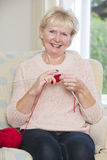 Portrait Of Senior Woman Sitting In Chair Knitting Stock Photos