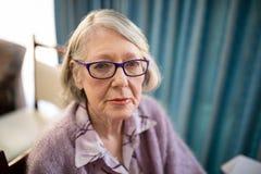 Portrait of senior woman sitting on chair at nursing home Stock Photo