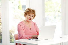 Portrait of senior woman. Sitting at desk and surfing on internet with laptop Stock Photo