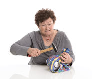 Portrait: senior woman smashing her piggy box. Isolated over whi Stock Photos