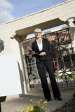 Portrait of a senior woman standing with clipboard in front of entrance gate stock photography