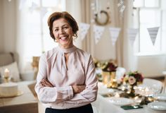 A portrait of a senior woman standing indoors in a room set for a party. stock photo