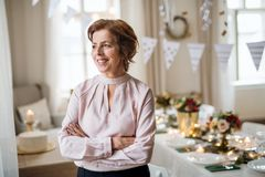 A portrait of a senior woman standing indoors in a room set for a party. A portrait of a senior woman standing indoors in a room set for a party, arms crossed stock photography