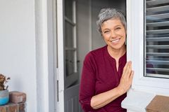 Happy senior woman leaning at door. Portrait of senior woman standing while leaning against door at home and looking at camera. Smiling mature woman standing at stock images