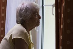Portrait of senior woman standing at the window Stock Photo