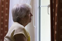 Portrait of senior woman standing at the window Stock Image
