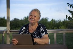Portrait of senior woman with tablet computer on veranda outdoor stock photo