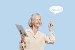 Portrait of senior woman with tablet PC pointing at tweet bubble against blue background Stock Photos