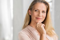 Satisfied mature woman. Portrait of a senior woman thinking with hand on chin and looking away. Mature smiling woman feeling happy. Thoughtful retired woman royalty free stock image