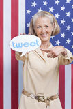 Portrait of senior woman with tweet bubble against American flag Royalty Free Stock Image