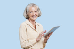 Portrait of senior woman using tablet PC against blue background Stock Photo