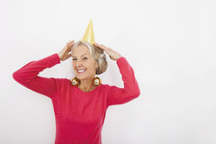 Portrait of senior woman wearing party hat and Christmas ornaments over white background Royalty Free Stock Photos