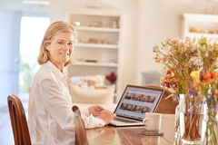 Portrait of a senior woman working on laptop at home. Smiling senior woman turning to look at the camera while sitting at a wooden table in a bright and tidy Royalty Free Stock Photography