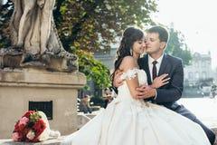 Portrait sensible des couples adorables de nouveaux mariés souriant et étreignant tendrement sur la vieille fontaine Image libre de droits