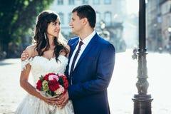 Portrait sensible des couples heureux de nouveaux mariés étreignant et regardant aux yeux de l'eadh autre dans la rue de ville Photos stock
