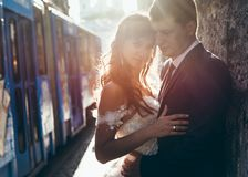 Portrait sensible des couples heureux de nouveaux mariés étreignant et se penchant sur le mur au fond du tram moteur Photo stock