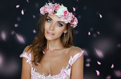 Portrait of a sensual beautiful girl in a pink dress and a wreath of flowers, beauty, close-up, on a dark background, with flying stock images