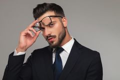 Portrait of sensual businessman taking eyeglasses off. And looking seductively on grey background Royalty Free Stock Photography