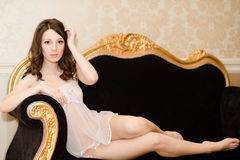 Portrait of sensual elegant beautiful girl on luxury couch Royalty Free Stock Photo