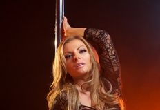 Portrait of a sensual female with blond hair with dance pole Stock Image