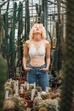 Sensual caucasian female model surrounded by succulent of all si. Portrait of a sensual female model wearing perky crochet top and jeans, posing among cacti with stock images