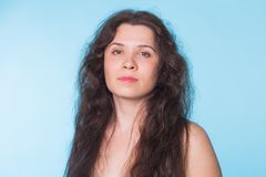 Portrait of sensual nude woman with curly hair on blue background Royalty Free Stock Photos