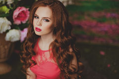 Portrait of sensual redhead young girl on floral background Stock Photo