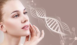 Portrait of sensual woman in DNA chains. Over beige background royalty free stock photography