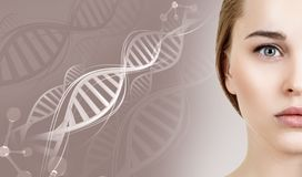 Portrait of sensual woman among DNA chains. Over beige background stock photo