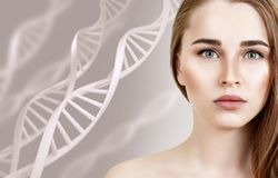 Portrait of sensual woman among DNA chains. Over beige background stock image