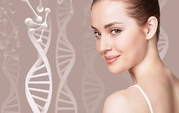 Portrait of sensual woman among DNA chains. Over beige background royalty free stock photo