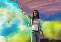 Portrait of a sensual woman making colorful smoke. Portrait of a sensual woman making colorful fume Stock Image