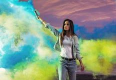 Portrait of a sensual woman making colorful smoke stock image