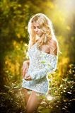 Portrait of a sensual young blonde female on field in sexy white short dress Stock Photos