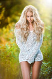 Portrait of a sensual young blonde female on field in white short dress Stock Images