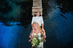 Portrait of a sensual young couple hugging on a wooden bridge. On a background of blue water, lifestyle, love, romance, relationships Stock Image