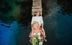 Portrait of a sensual young couple hugging on a wooden bridge. On a background of blue water, lifestyle, love, romance, relationships Royalty Free Stock Photography