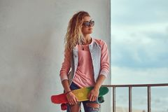 Portrait of a sensual young girl with blonde hair in sunglasses dressed in a pink jacket standing near a guardrail royalty free stock photography